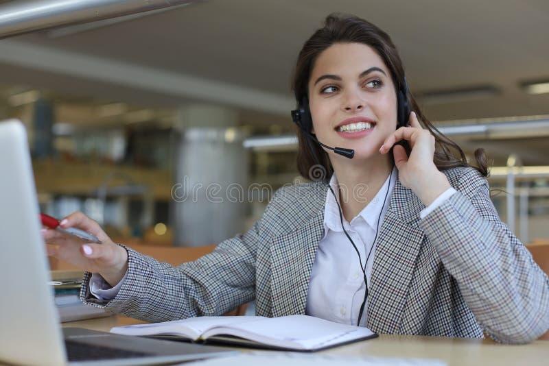 Оператор работы с клиентом женщины со шлемофоном и усмехаться стоковые изображения