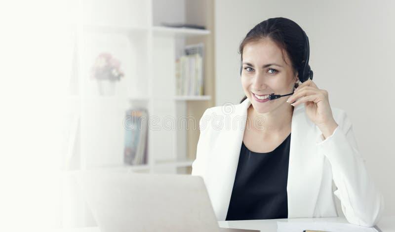 Оператор работы с клиентом женщины счастливый усмехаясь со шлемофоном стоковая фотография