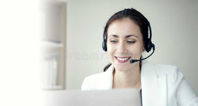Оператор работы с клиентом женщины счастливый усмехаясь со шлемофоном стоковые изображения rf