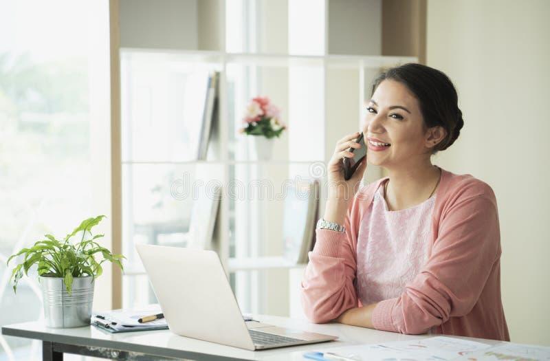 Оператор работы с клиентом женщин счастливый усмехаясь с мобильным телефоном стоковая фотография