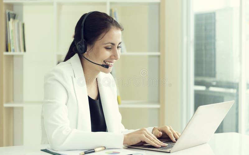 Оператор работы с клиентом женщин счастливый усмехаясь со шлемофоном E стоковые фотографии rf