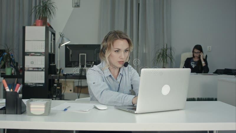 Оператор работы с клиентом работая в офисе центра телефонного обслуживания стоковое фото
