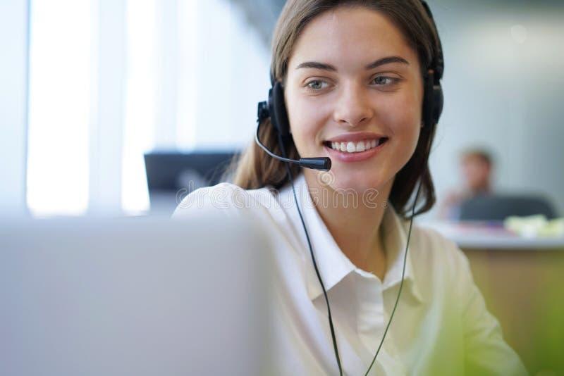 Оператор работы с клиентом работая в офисе центра телефонного обслуживания стоковые фотографии rf