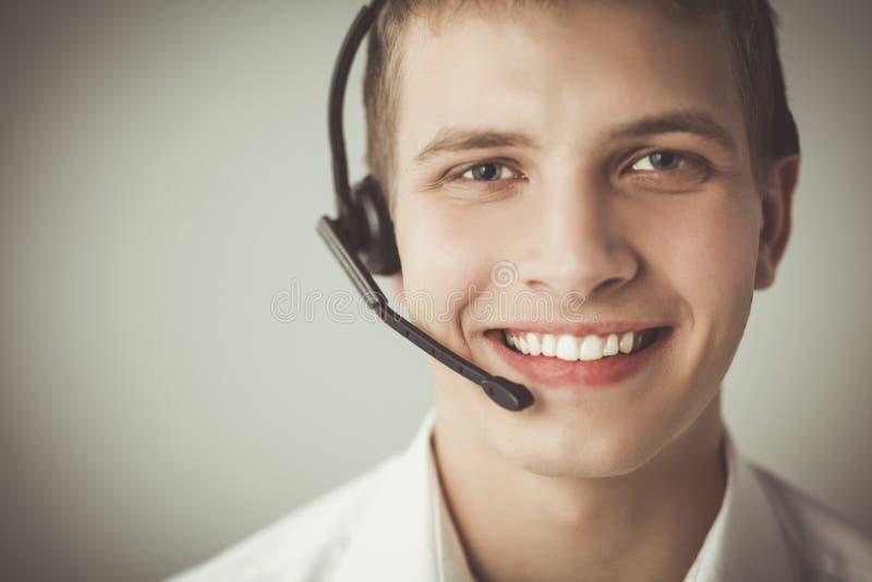 Оператор работы с клиентом с шлемофоном на белой предпосылке стоковое фото rf