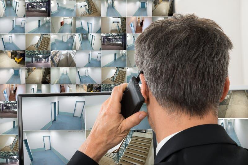 Оператор системы безопасности смотря отснятый видеоматериал cctv стоковая фотография