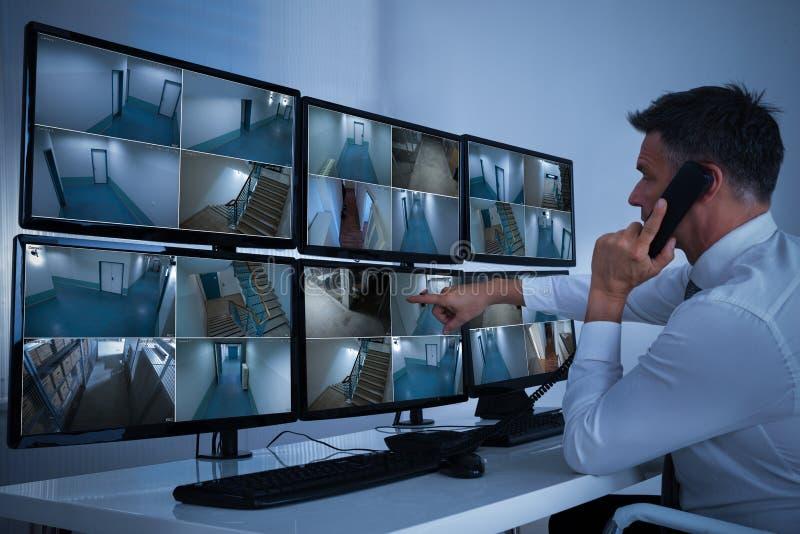 Оператор системы безопасности смотря отснятый видеоматериал cctv стоковая фотография rf