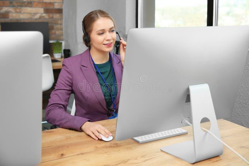 Оператор службы технической поддержки работая со шлемофоном и компью стоковые изображения