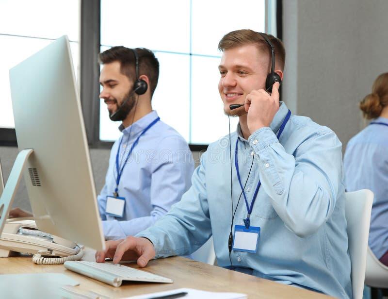 Оператор службы технической поддержки работая с коллегами стоковые изображения