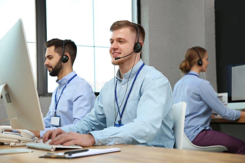Оператор службы технической поддержки работая с коллегами стоковые изображения rf