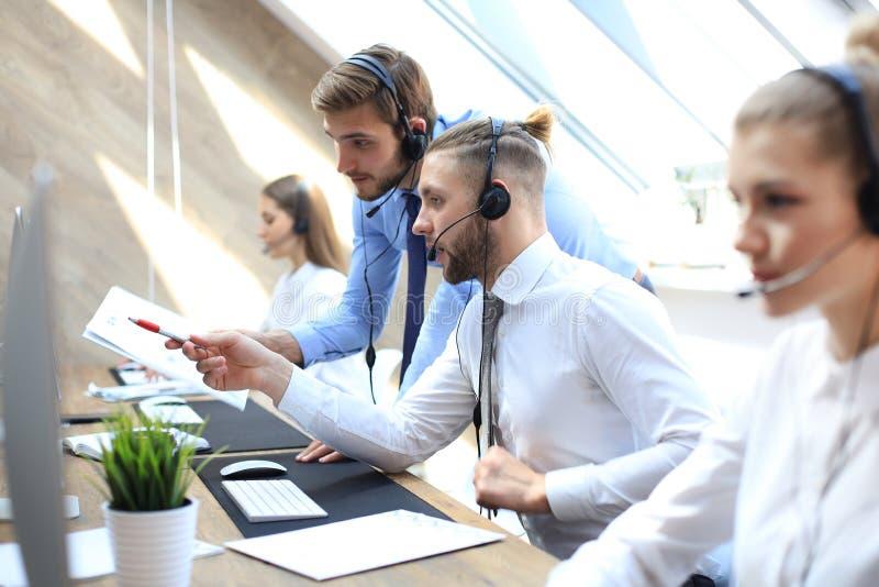 Оператор телефона работая на офисе центра телефонного обслуживания помогая его коллеге стоковое фото