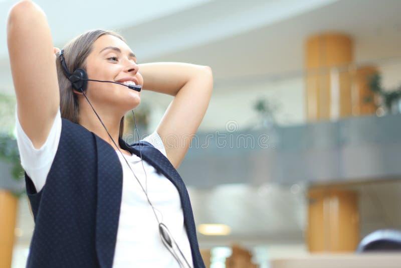 Оператор центра телефонного обслуживания в шлемофоне отдыхая на рабочем месте в офисе стоковые фотографии rf