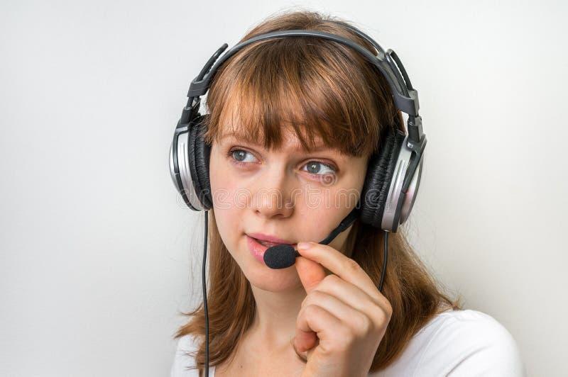 Оператор центра телефонного обслуживания с шлемофоном на рабочем месте в центре телефонного обслуживания стоковое фото