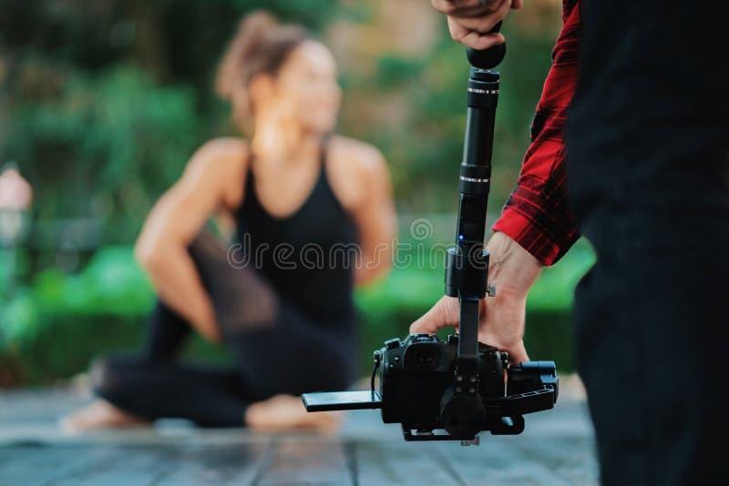 Оператор человека видеокамеры работая при профессиональное оборудование, снимая запись Видео стрельбы оператора йоги стоковое изображение rf