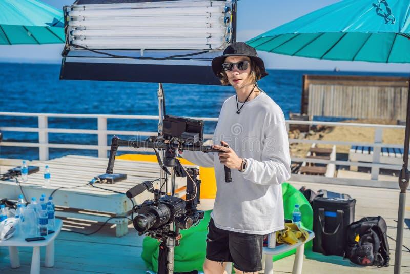 Оператор Steadicam и его ассистент подготавливают камеру и стабилизатор-карданный подвес 3 осей для коммерчески всхода стоковое изображение rf