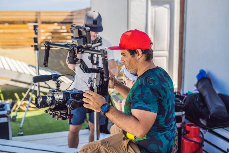 Оператор Steadicam и его ассистент подготавливают камеру и стабилизатор-карданный подвес 3 осей для коммерчески всхода стоковая фотография