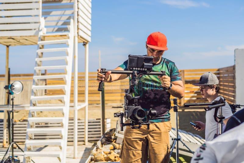 Оператор Steadicam и его ассистент подготавливают камеру и стабилизатор-карданный подвес 3 осей для коммерчески всхода стоковое фото rf