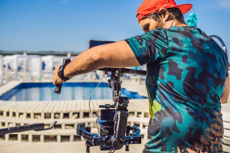 Оператор Steadicam и его ассистент подготавливают камеру и стабилизатор-карданный подвес 3 осей для коммерчески всхода стоковое фото