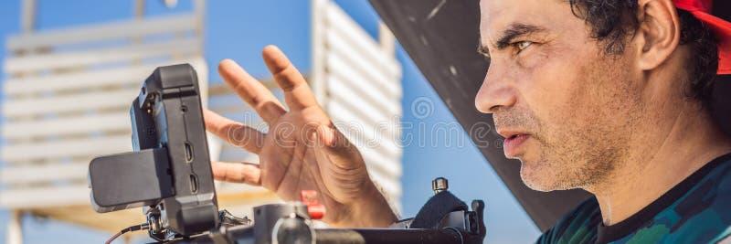 Оператор Steadicam и его ассистент подготавливают камеру и стабилизатор-карданный подвес 3 осей для коммерчески ЗНАМЕНИ всхода, Д стоковые фотографии rf