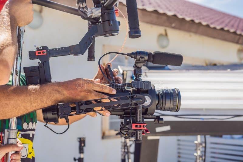Оператор Steadicam подготавливает камеру и стабилизатор-карданный подвес 3 осей для коммерчески всхода стоковая фотография rf