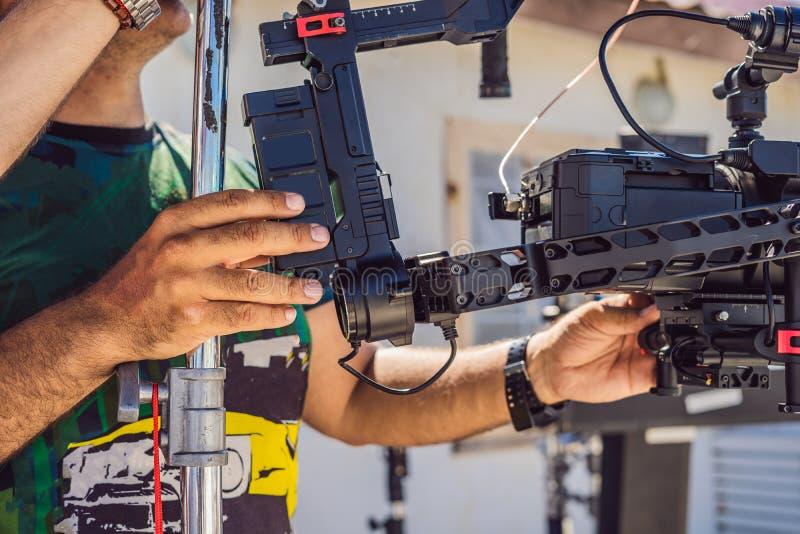 Оператор Steadicam подготавливает камеру и стабилизатор-карданный подвес 3 осей для коммерчески всхода стоковые фотографии rf