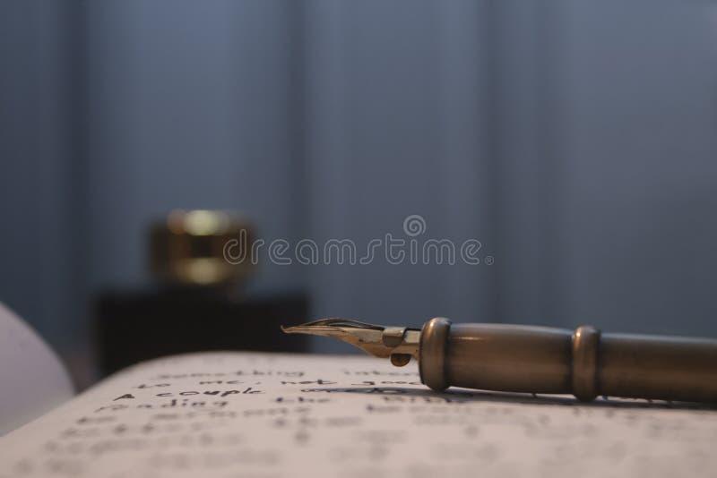 Оперитесь ручка на странице с текстом и чернилами в расплывчатой предпосылке стоковые изображения
