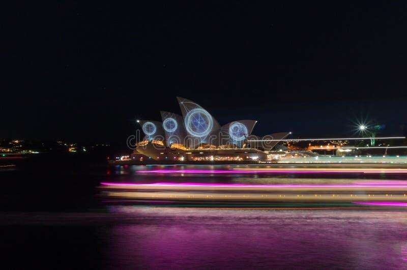 Оперный театр Сиднея загоренный во время яркого фестиваля света Сиднея со световым эффектом нерезкости движения шлюпки круиза стоковое фото