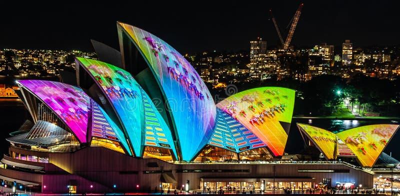 Оперный театр Сиднея освещенный вверх вечером на ярком светлом фестивале - близком вверх стоковая фотография rf