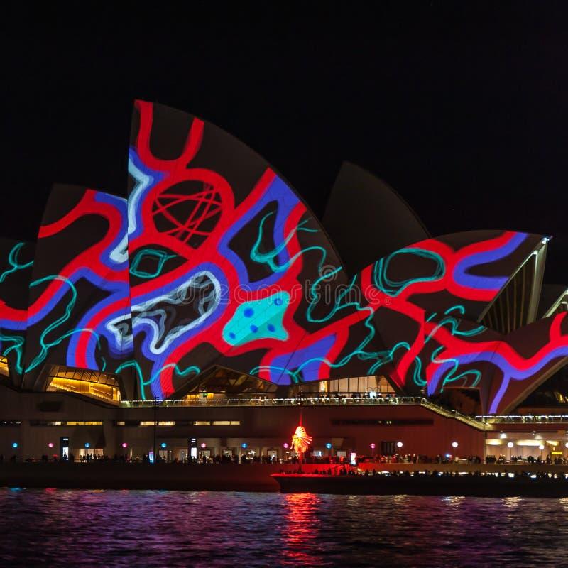 Оперный театр Сиднея освещенный вверх вечером с картинами на ярком св стоковые фото