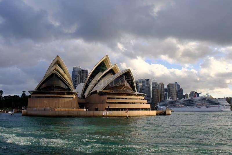 Оперный театр Сиднея, свет захода солнца и темные облака, Австралия стоковые изображения