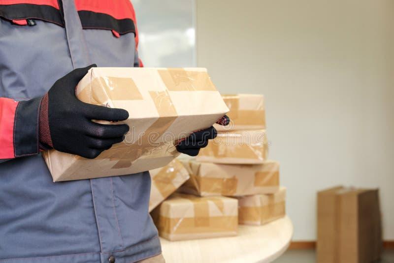 Опечатанный пакет в руках сотрудника по доставке стоковое фото rf
