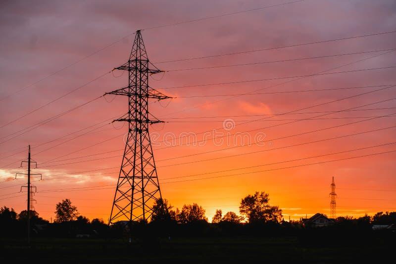 Опора, высоковольтная предпосылка неба башни Красивый красочный заход солнца стоковые фото