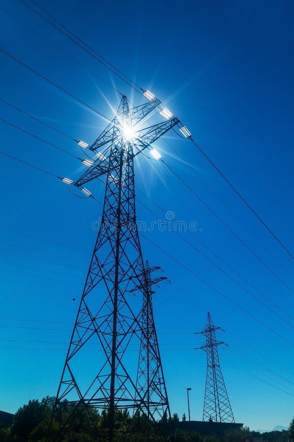 Опора электричества против света стоковое фото