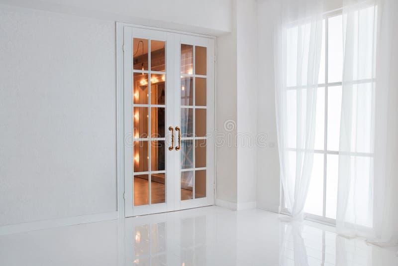 Опорожните белую комнату с большим окном и стеклянную французскую дверь с яркими оранжевыми светами стоковые фотографии rf