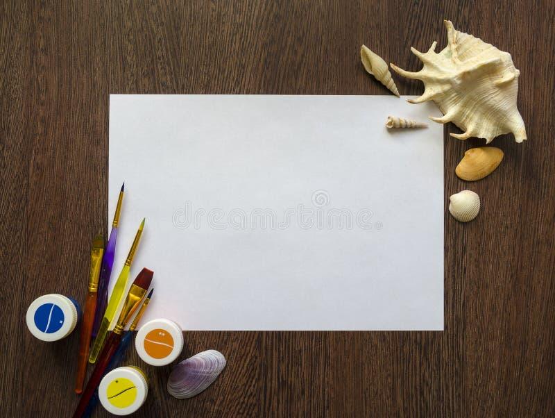 Опорожните белый лист бумаги для вашего текста на темной деревянной предпосылке таблицы Пестрые краски, раковины, щетки вокруг ег стоковые изображения rf