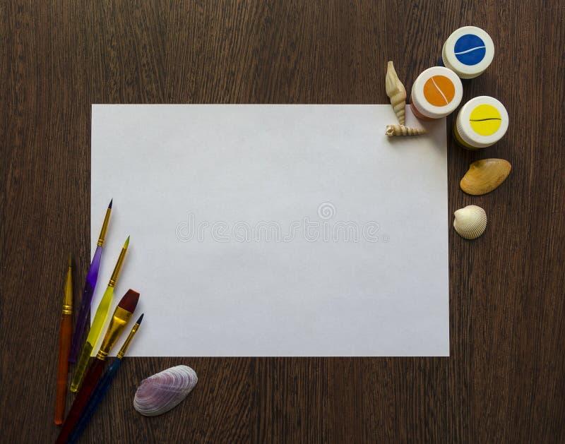 Опорожните белый лист бумаги для вашего текста на темной деревянной предпосылке таблицы Пестрые краски, раковины, щетки вокруг ег стоковая фотография rf