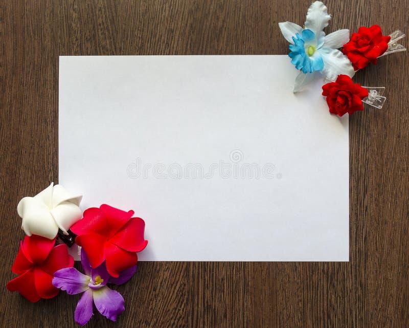 Опорожните белый лист бумаги для вашего текста на темной деревянной предпосылке таблицы Пестротканые цветки и бабочки вокруг его стоковое фото rf