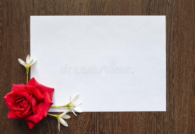Опорожните белый лист бумаги для текста на темной деревянной предпосылке Предпосылка с рамкой цветков стоковое изображение