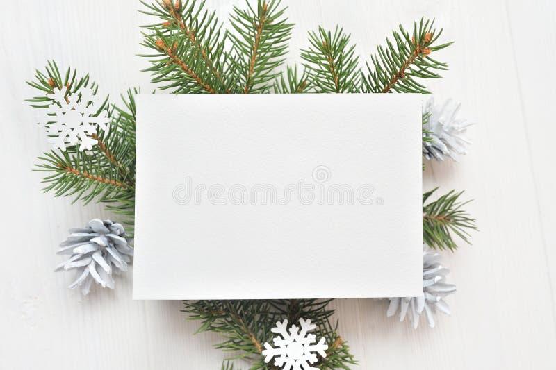 Опорожните белый лист бумаги на предпосылке белого рождества ветвей и конусов ели Письмо на xmas, модель-макет Плоское положение  стоковое изображение rf