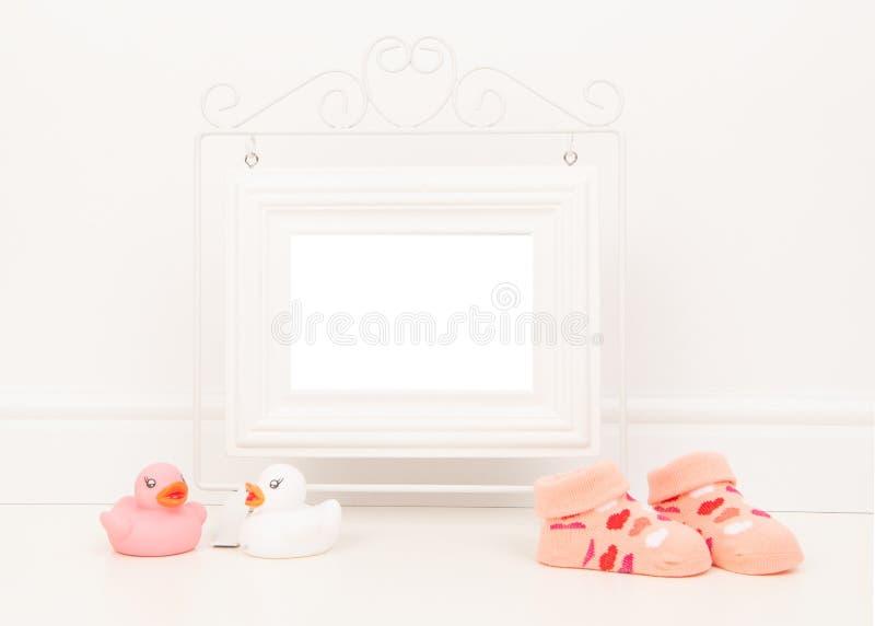 Опорожните белую картинную рамку с космосом для текста или желания в белой установке живущей комнаты с розовым носком младенца и  стоковые фотографии rf