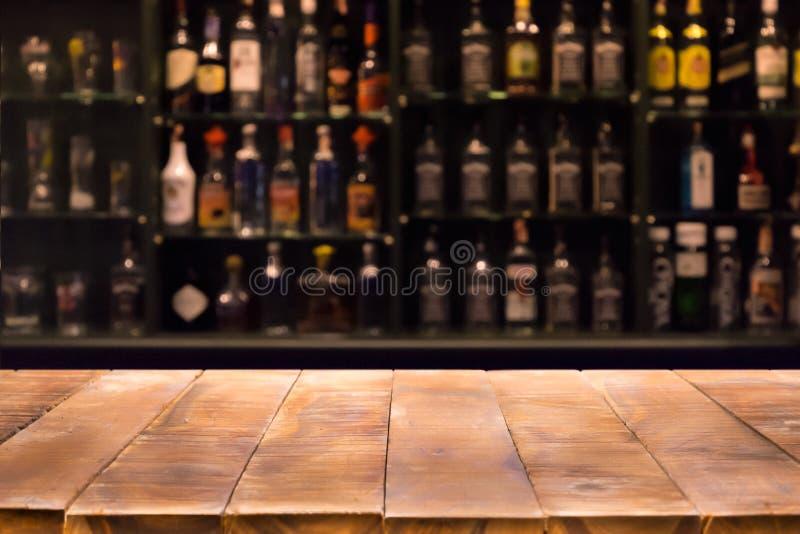 Опорожните деревянный счетчик бара с defocused предпосылкой и бутылки ресторана стоковая фотография rf