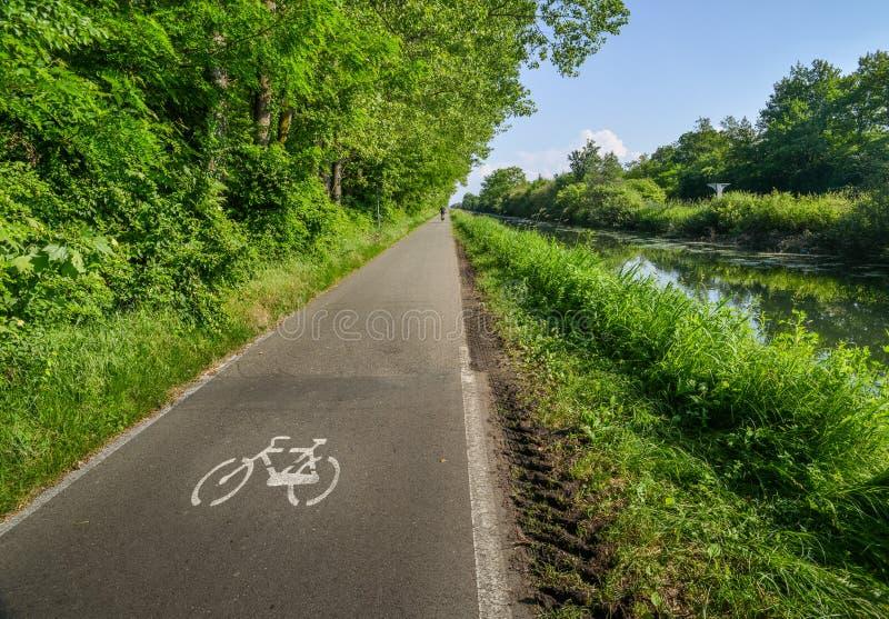 Опорожните задействуя путь вдоль Naviglio Pavese, канала который протягивает для 30km от Павии к милану, Италии стоковые фотографии rf
