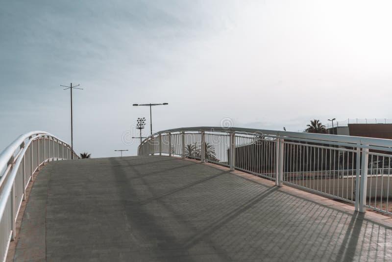 Опорожните изогнутый пешеходный мост с тропой в di форума Барселоны стоковые фотографии rf