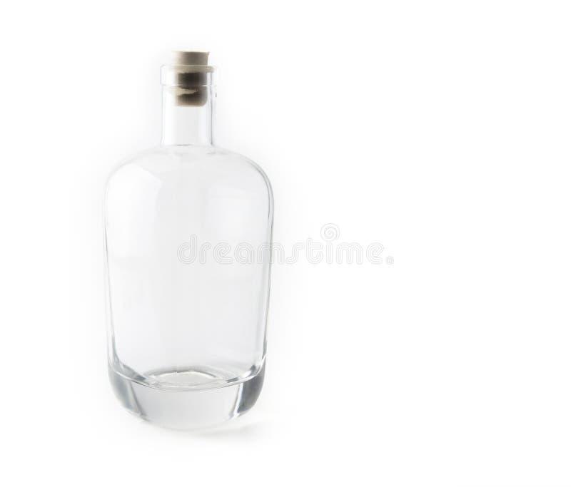 Опорожните стеклянную бутылку с пробочкой на белизне стоковые фото