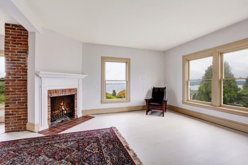 Опорожните традиционный интерьер комнаты в белых тонах с камином и половиком кирпича стоковая фотография rf