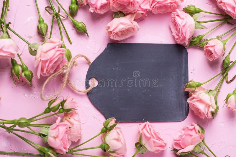 Опорожните черную бирку и розовые цветки роз на розовом текстурированном backg стоковое изображение rf
