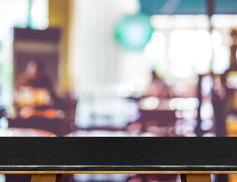 Опорожните черную мраморную таблицу и запачканную предпосылку света bokeh кафа стоковое фото