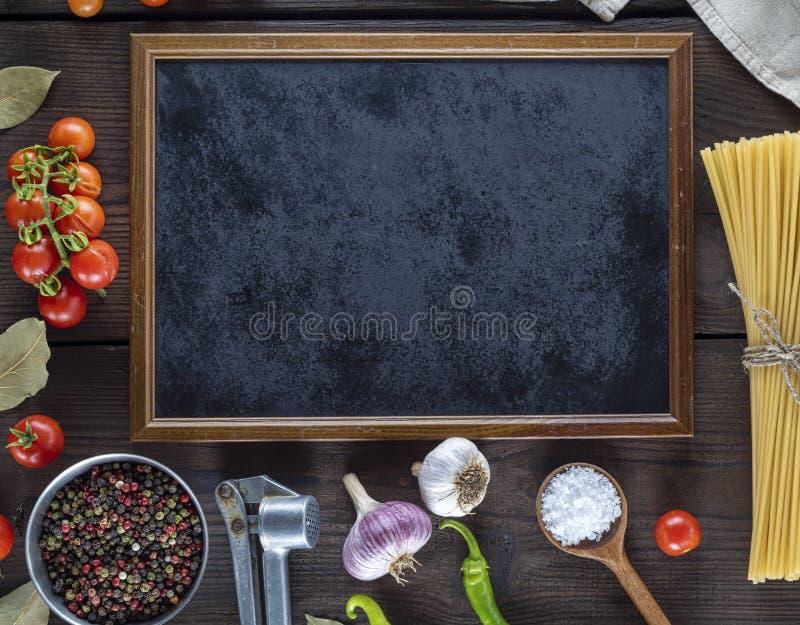 Опорожните черные рамку и ингридиенты для варить макаронные изделия стоковое фото rf