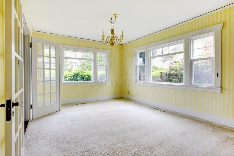 Опорожните dinning комнату с cream ковром и желтыми стенами стоковое фото