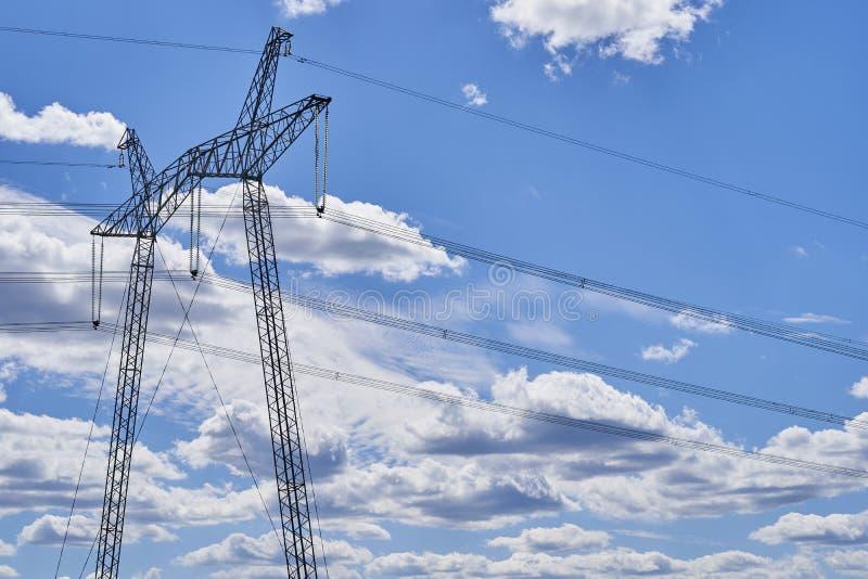 Опоры линии высокого напряжения против неба с облаками стоковые фото
