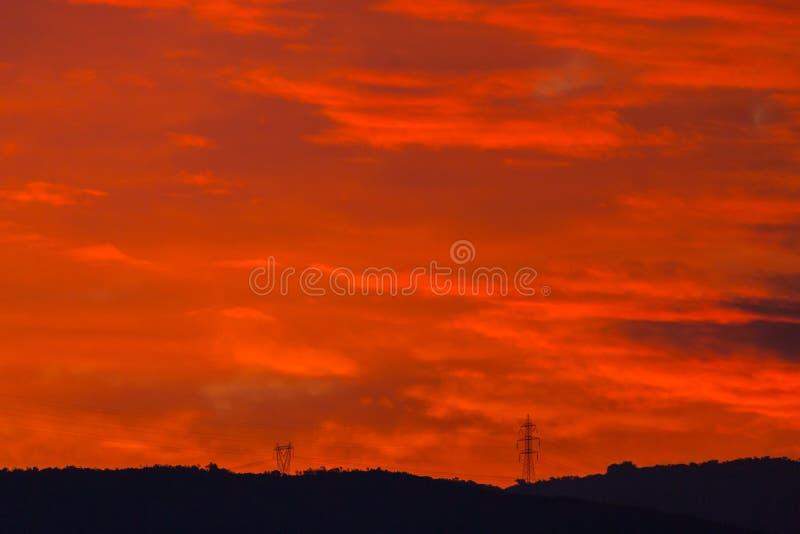 2 опоры электричества в небе красного цвета захода солнца стоковое изображение rf